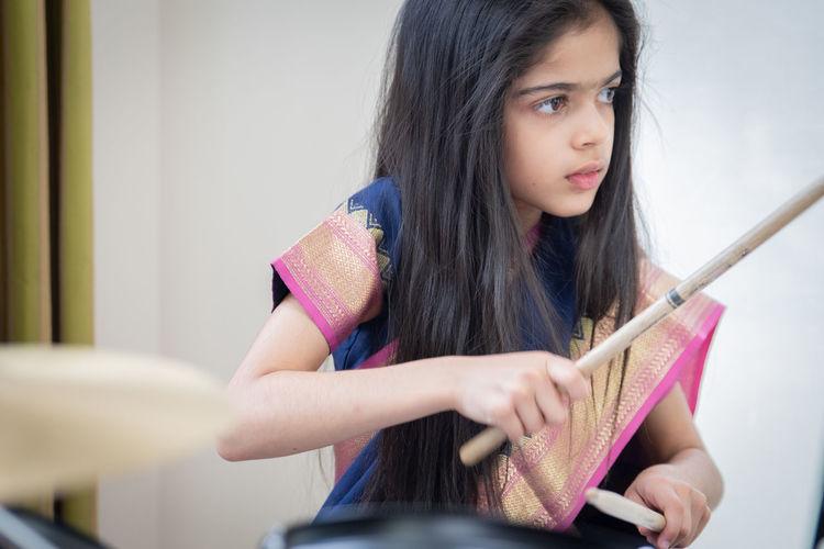 Girl in sari playing drum