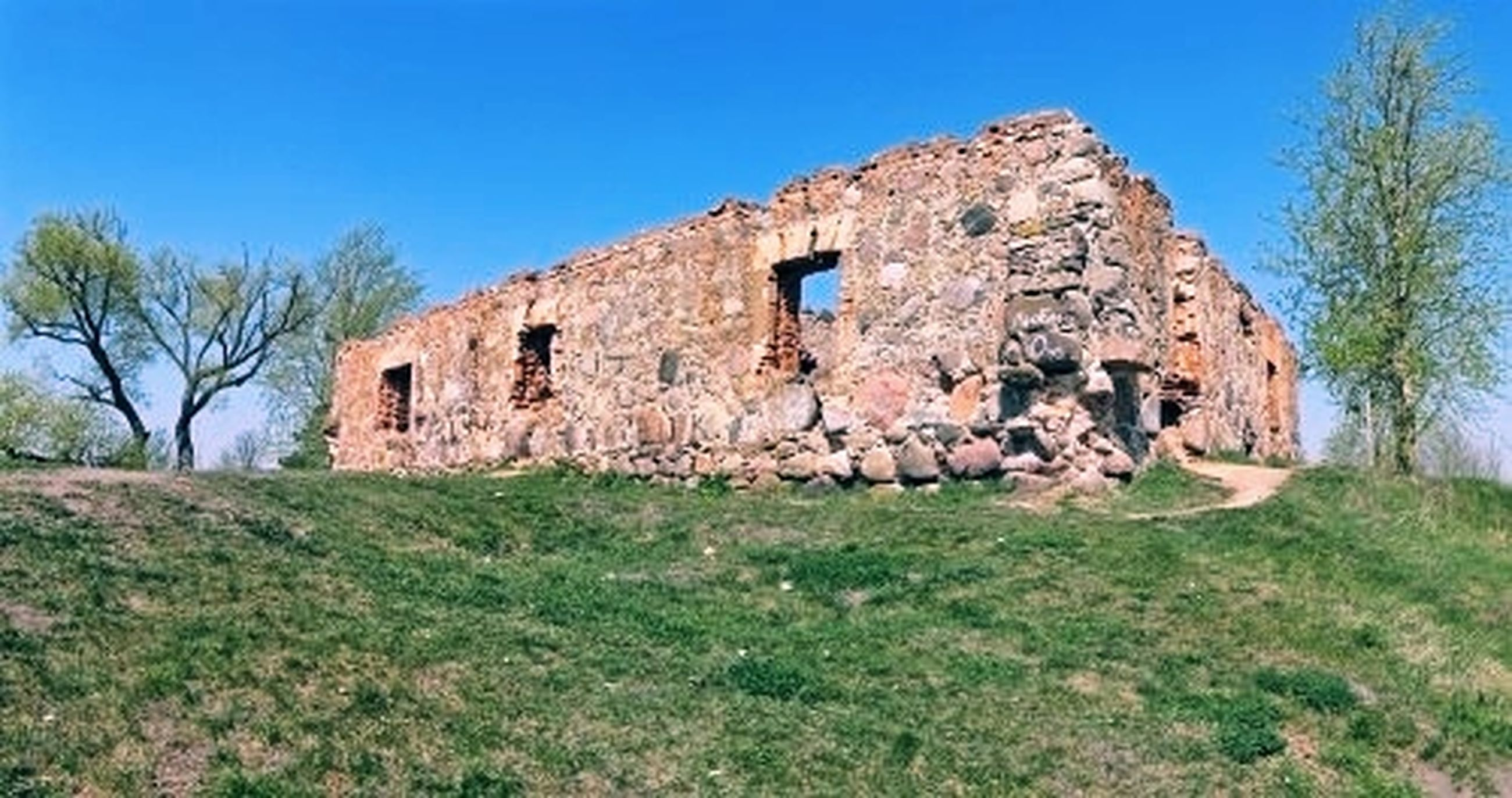architecture, plant, sky, history, nature, ruins, the past, grass, built structure, land, old ruin, landscape, tree, clear sky, blue, no people, abandoned, old, building, building exterior, ancient, travel destinations, ruined, damaged, scenics - nature, fortification, day, field, outdoors, travel, wall, environment, house, rural scene, non-urban scene, rundown, ancient history, stone material, village, weathered, green, rural area, tranquility, rock, tourism, bad condition, sunny