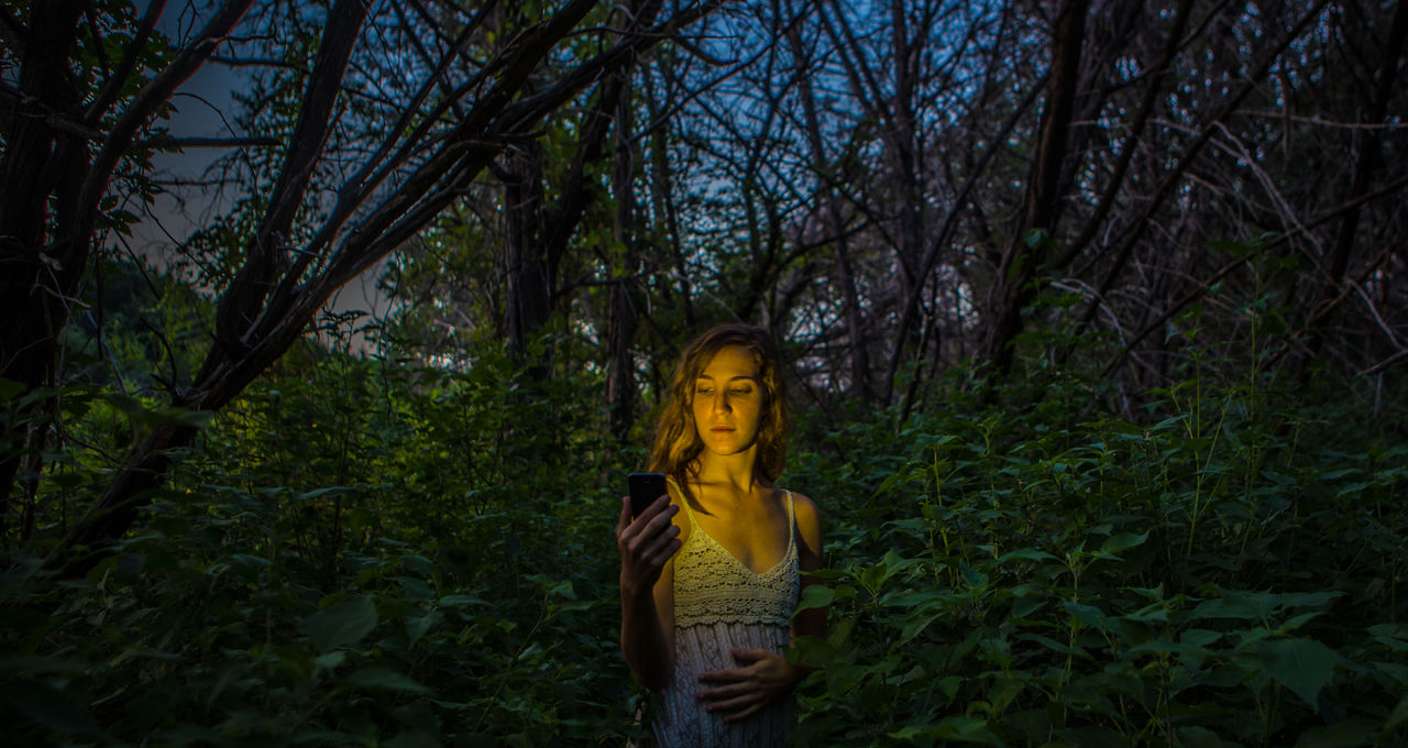 Beautiful woman using phone in forest at night