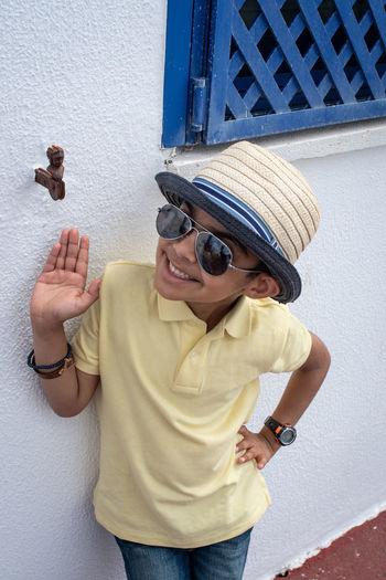 Boy wearing hat standing by wall