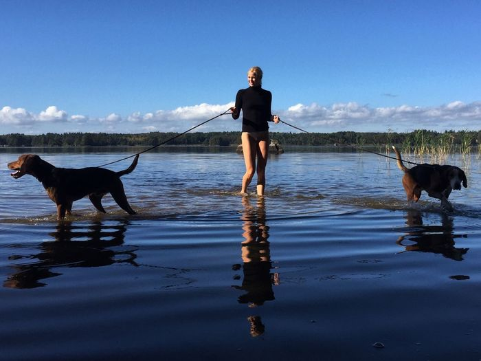 Portrait of young woman with dog standing on lake against sky