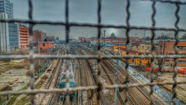 Fence Metal Protection Chainlink Fence Focus On Foreground Sky Architecture Built Structure Day Outdoors Close-up No People Transportation Train Morgen Instafamous Tagstagramers Colours Photography Instatrees Italy Rail Railroad Station Platform Nature Adapted To The City