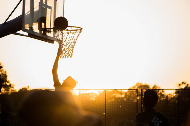 Basketball - Sport Basketball Hoop Basketball Player Childhood Clear Sky Close-up Competition Competitive Sport Court Day Leisure Activity Net - Sports Equipment One Person Outdoors People Playing Real People Silhouette Sky Sport Sunlight Sunset