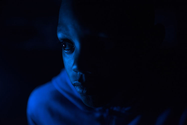 Side eye African Adult Aggression  Black Background Blue Body Part Close-up Dark Fear Front View Headshot Human Body Part Human Face Illuminated Indoors  Light - Natural Phenomenon Mystery One Person Portrait Spooky Studio Shot