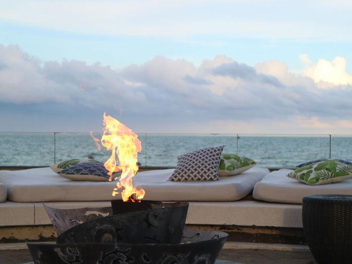 Bonfire on beach by sea against sky