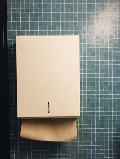 Towel dispenser on tiled wall in bathroom