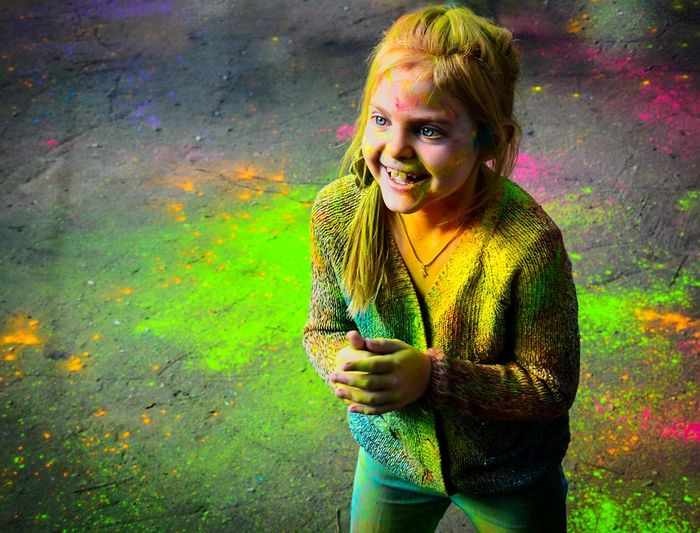 Portrait of a smiling young girl covered in paint powder