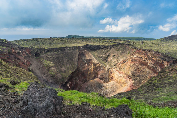 Volcanic crater at izu oshima island against cloudy sky