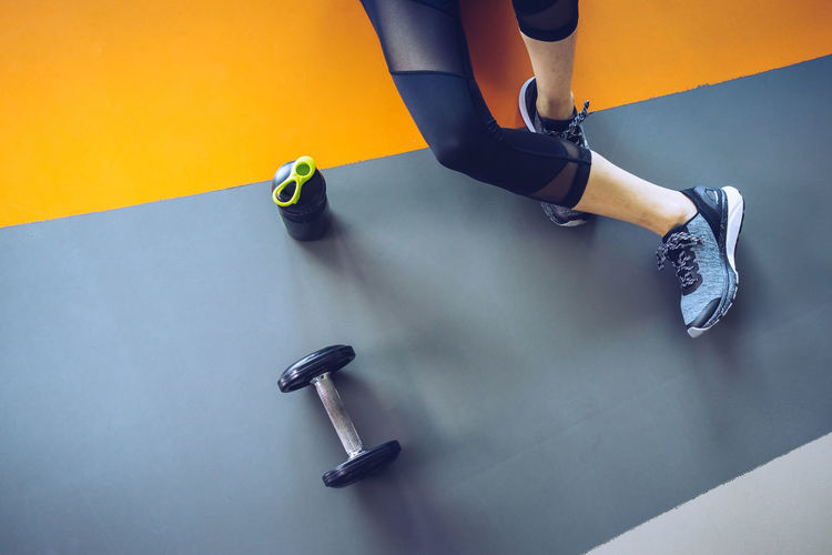 Low Section Of Woman Sitting By Water Bottle And Dumbbell On Floor