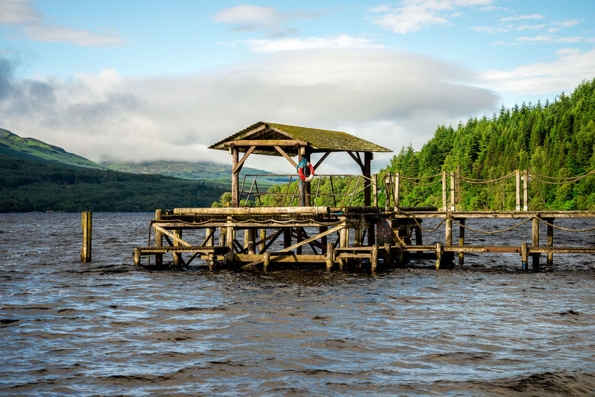 A wooden jetty at Loch Tay Highland Lodges boat station, central Scotland Boat Station Family Good Weather Hills Holiday Loch Tay Pier Scotland Tourist Attraction  Trees Calm Water Cloud Sky Forest Highlands Jetty Killin  Lake View Lakeshore Landscape Sailing Boat Summer Travel Destinations Vacation Wooden Yacht