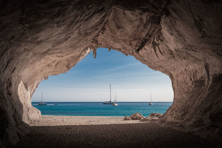 Scenic view of sea against sky seen through cave
