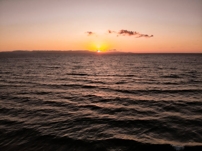 Scenic view of sea against romantic sky at sunset
