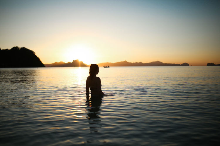 Silhouette Water Sky Sunset Beauty In Nature Waterfront One Person Silhouette Scenics - Nature Real People Tranquility Tranquil Scene Leisure Activity Nature Sea Lifestyles Reflection Idyllic Outdoors Ocean Woman Girl