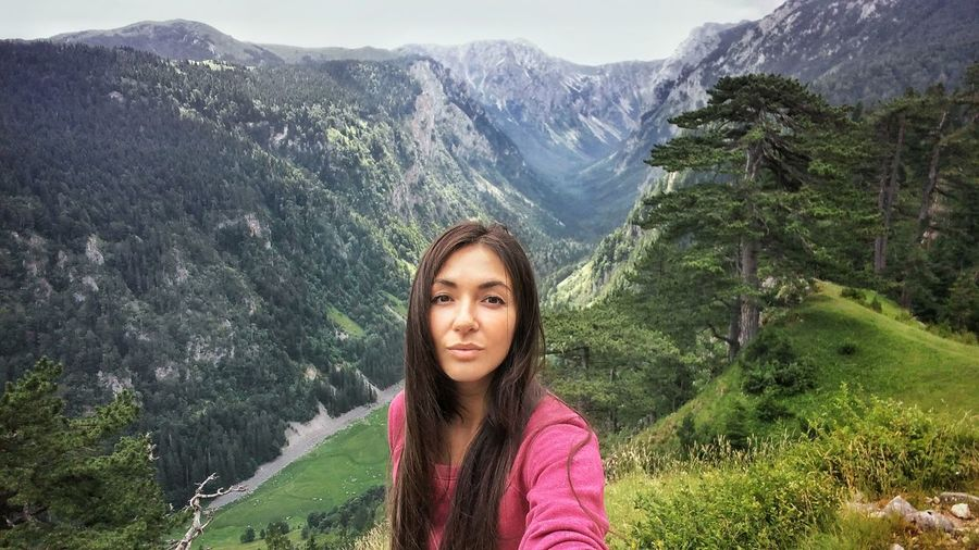Portrait of young woman standing against mountains
