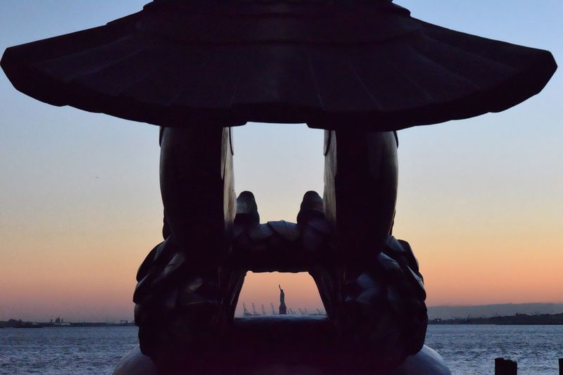 Silhouette Statue Of Liberty Seen Through Navy Memorial Eagle At Battery Park During Sunset