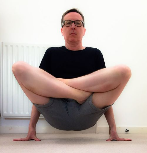 Full length of man practicing yoga against white wall