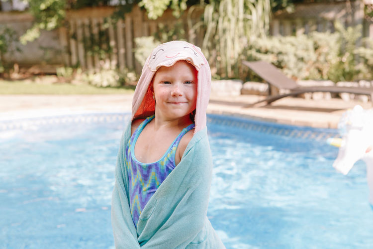 Portrait of smiling girl standing in swimming pool