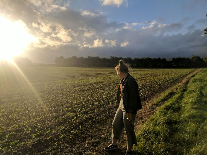Full length of woman standing on agricultural field during sunset