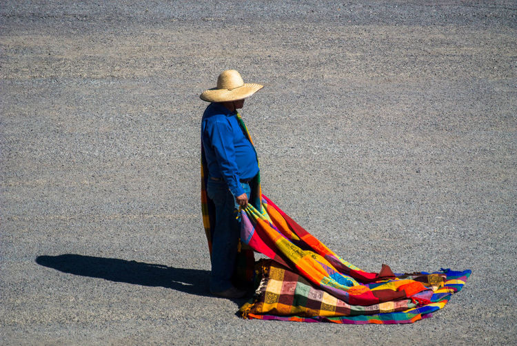 Side view of man wearing sombrero holding multi colored blanket while standing on street