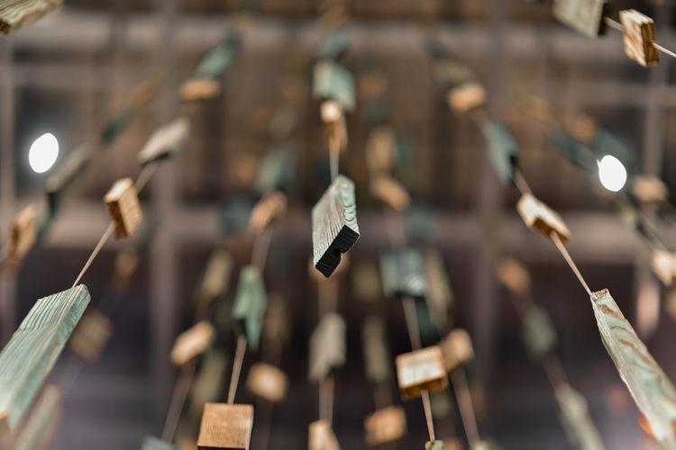 Close-up of wooden bricks hanging on metal grate