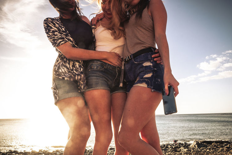 Midsection of young friends standing at beach against sky