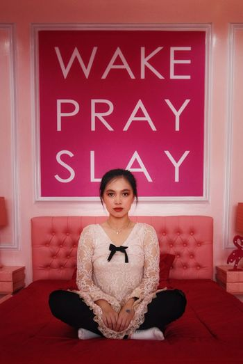 Portrait of a young attractive woman sit against wake pray slay quotes on the wall