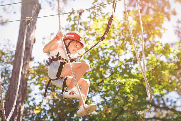 Young girl climbing in forest rope climbing park Climbing Climbing Park Day Family Activity Forest Rope Park Helmet Leisure Activity Lifestyles Nature One Person Outdoors Protection Real People Rope Safety Safety Harness Summer Holiday Sunny Day Teambuilding Tree Summer Sports