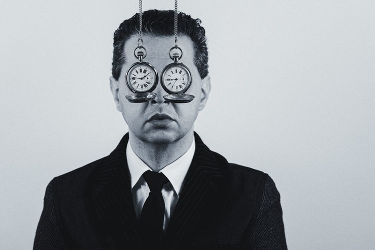 Portrait of man against white background with pocket watch in his eyes