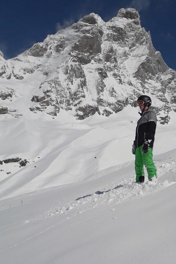 Young Man Snowboarding On Snowcapped Mountain Against Cloudy Sky
