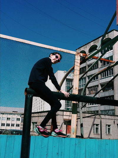 Full length of young woman balancing on railing against clear blue sky in city