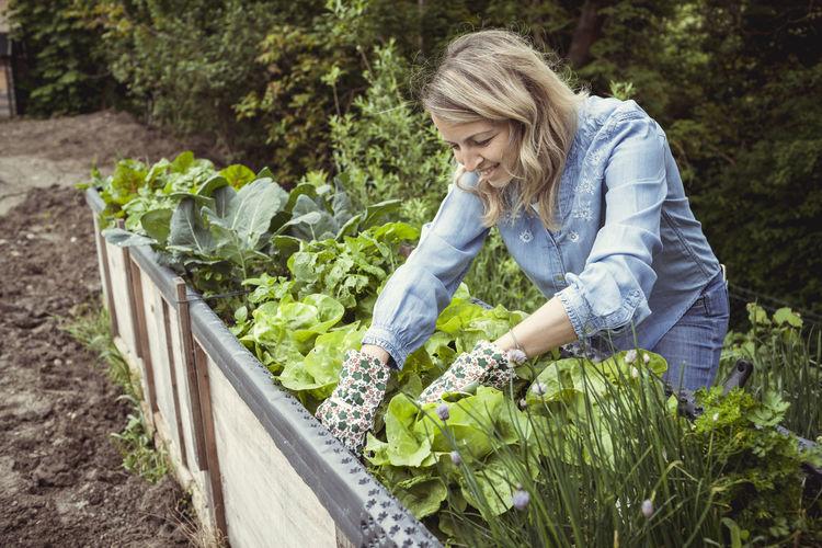 Woman standing by plants in farm