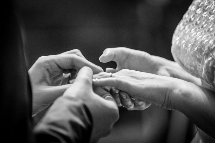 Cropped image of bridegroom putting ring in finger of bride