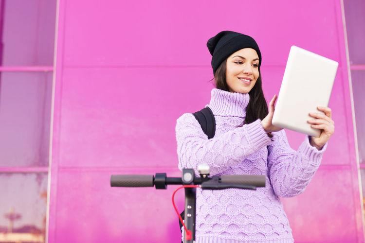 Young woman using phone while standing against pink wall