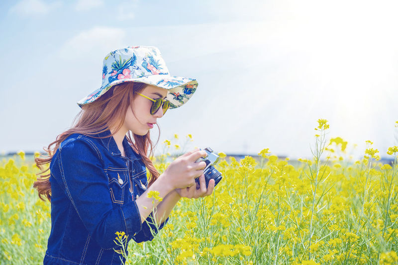 Side view of woman photographing at rape field