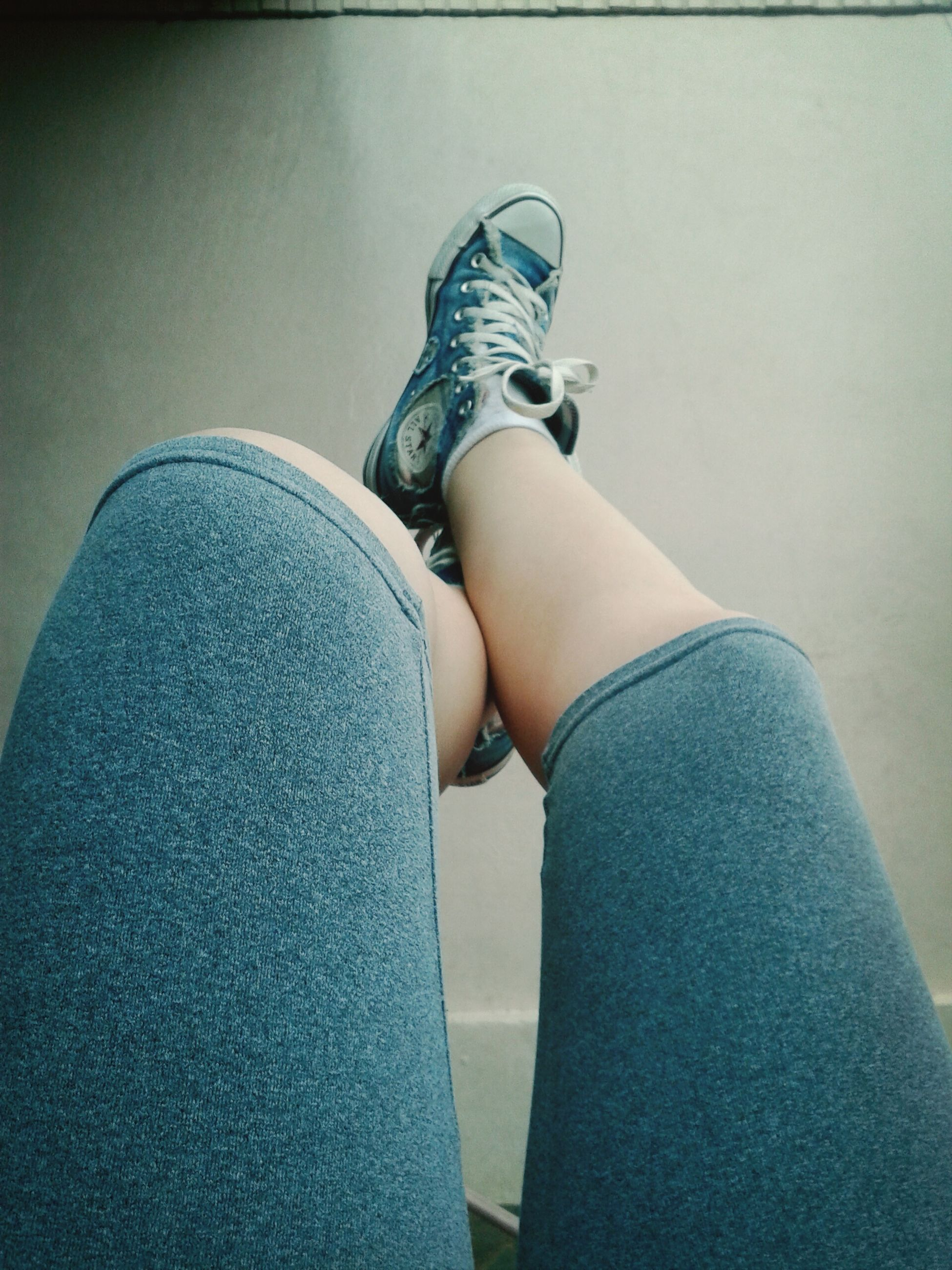 low section, person, shoe, jeans, indoors, lifestyles, casual clothing, sitting, footwear, leisure activity, relaxation, standing, human foot, personal perspective, blue, fashion