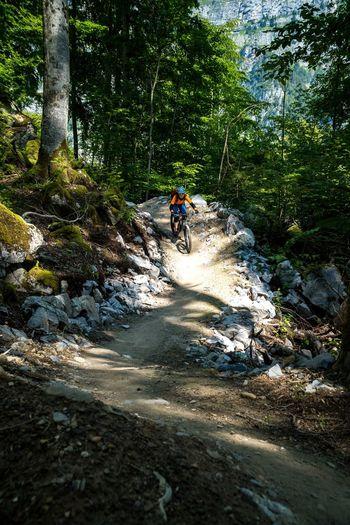 Woman riding a mountain bike on a flow trail in a bike park in glarus, switzerland.