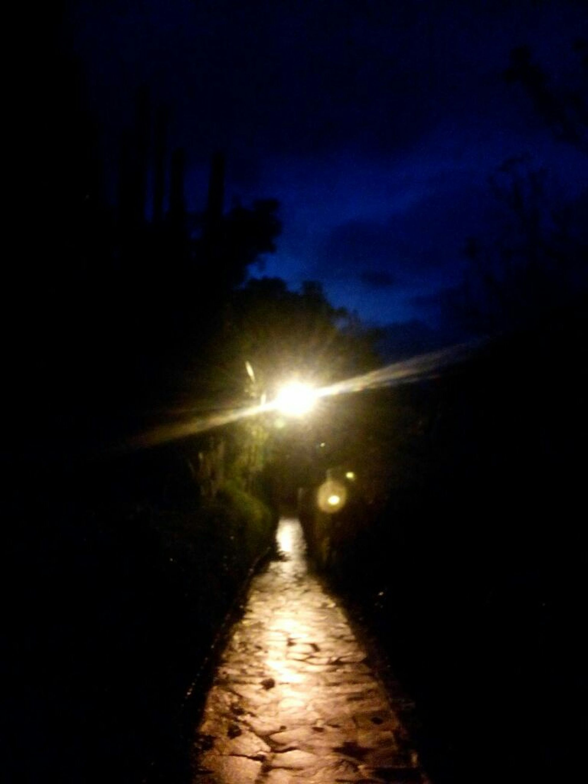 the way forward, night, sky, diminishing perspective, illuminated, vanishing point, silhouette, road, street, dark, street light, transportation, lens flare, sun, tranquility, nature, weather, outdoors, dusk, wet