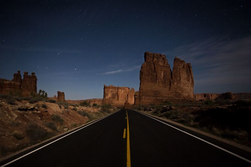 Road leading towards rock formation against sky at night