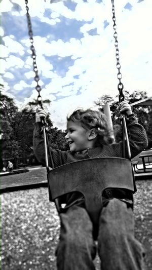 Cheerful Boy Enjoying On Swing At Park