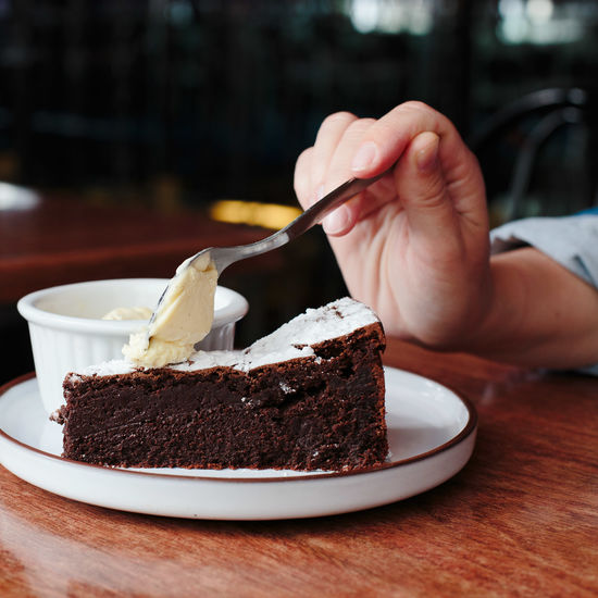 not healthy eating Cake Chocolate Cake Close-up Day Dessert Food Food And Drink Freshness Human Body Part Human Hand Indoors  Indulgence One Person People Plate Ready-to-eat Real People Serving Size SLICE Sweet Food Table Temptation Unhealthy Eating