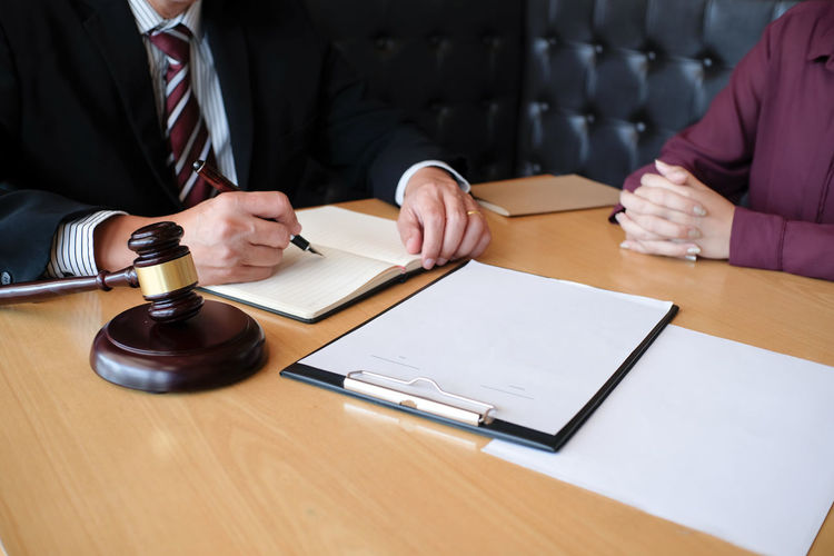 Midsection of judge and client discussing on table