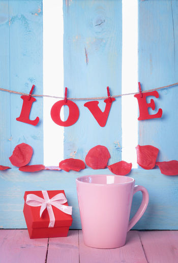 Red gift box near a pink cup with the word love spelled from red paper letters, tied to a string and soap rose petals on a blue wooden fence. Copy Space Hanging Letters Love Message Card Rose Petals Wooden Fence Blue Background Celebration Coffee Mug Gift Label Tag Mugs No People Petals Red Red Box Text Here Tied Bow