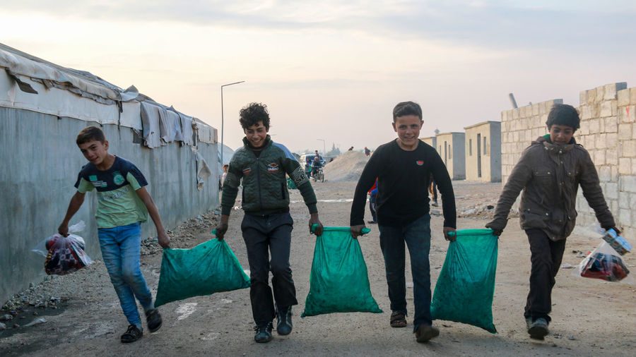 Full length of boys carrying supplies on street