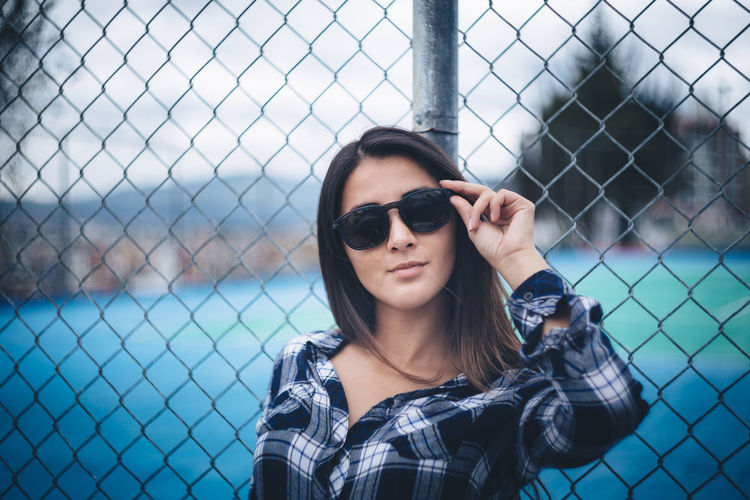Beautiful young woman wearing sunglasses leaning on chainlink fence