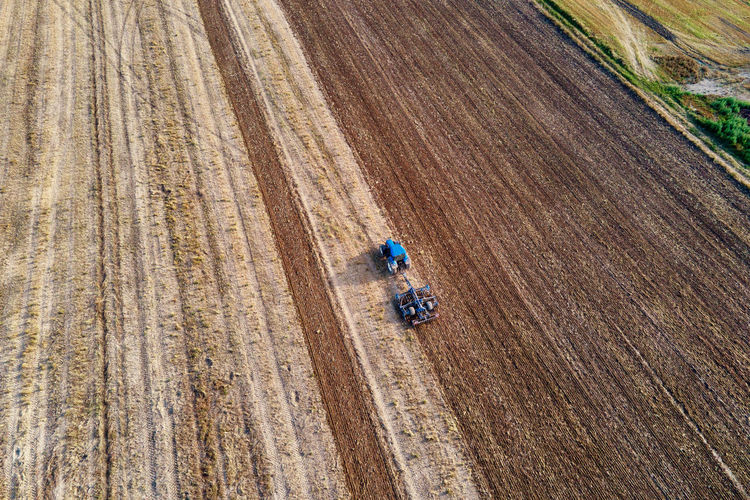 Tractor plows ground on cultivated farm field