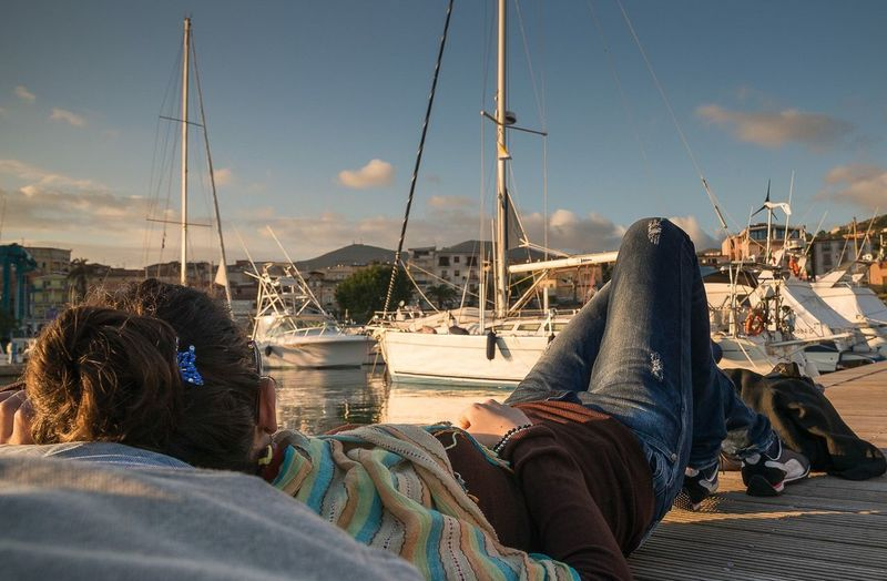 Low section of people relaxing on sailboats against sky