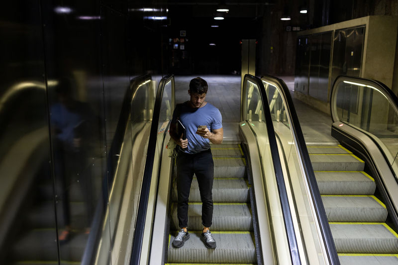 Full length of man standing on escalator