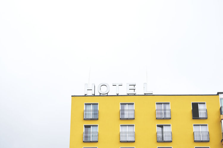 The Yellow Hotel At The White Place. EyeEmNewHere Modern Architecture Poster White Space Yellow House  Architecture Berliner Ansichten Building Exterior Built Structure Clear Sky Copy Space Discover Berlin Hitchcock Afternoon Hitchcock Style Hitchcockian Hostelscenary Hotel Hotel Life Low Angle View Modernism No People White Background White Color Windows Yellow