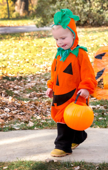 Full length of boy holding pumpkin decoration during autumn