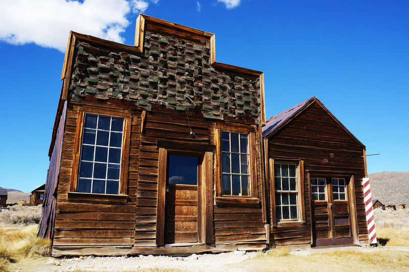 An old west barber shop and sheriff office in ghost town of Bodie. Architecture Blue Building Exterior Built Structure Closed Cloud Day Deterioration Exterior Façade Ghost Town No People Old Outdoors Run-down Sky Sunny The Old West